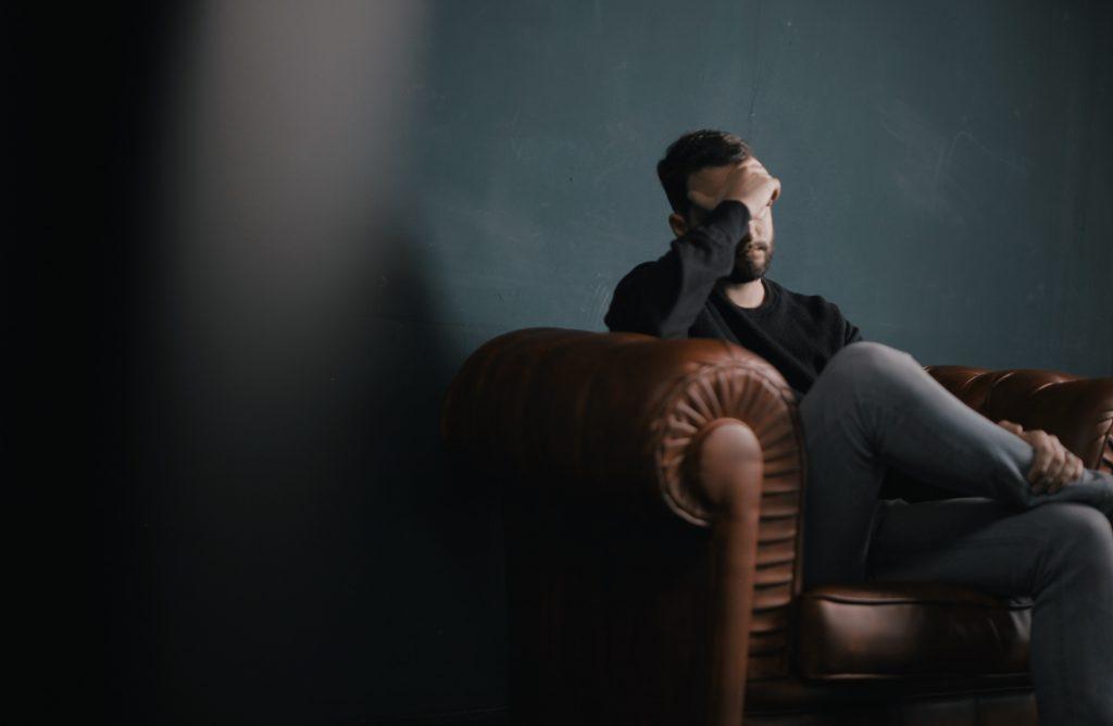Dejected man sitting on sofa